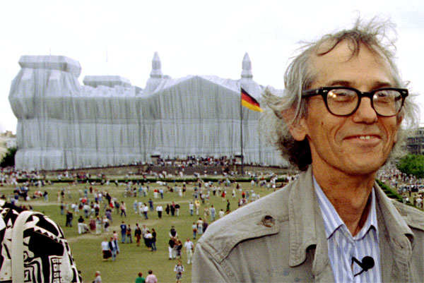 Christo poses for photographers in front of the wrapped Reichstag, in Berlin, Germany, June 26, 1995