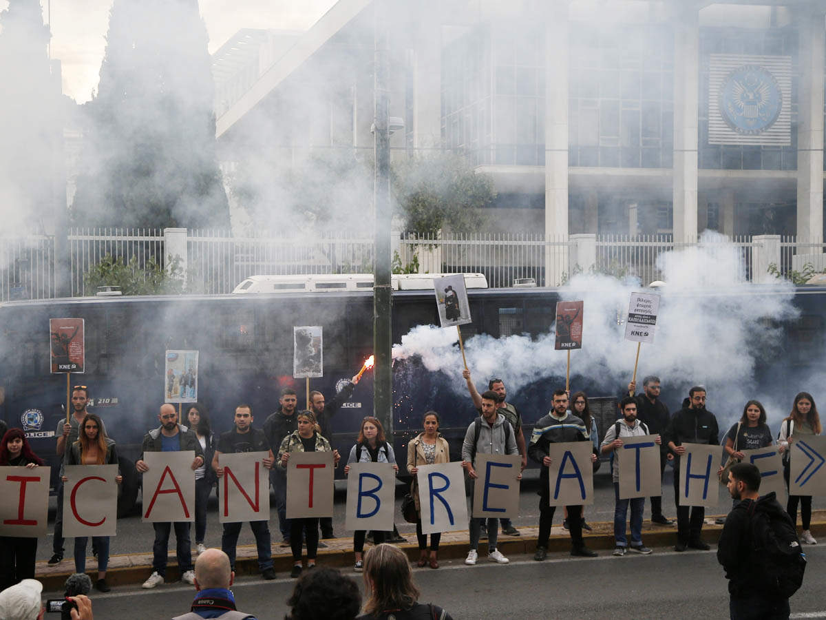 Members of the Greek Communist Party (KKE) youth organisation, hold up flares and placards reading 'I cant breathe', as they stand outside the U.S. embassy in Athens, Monday, June 1, 2020, to protest against the killing of George Floyd in Minneapolis, USA.