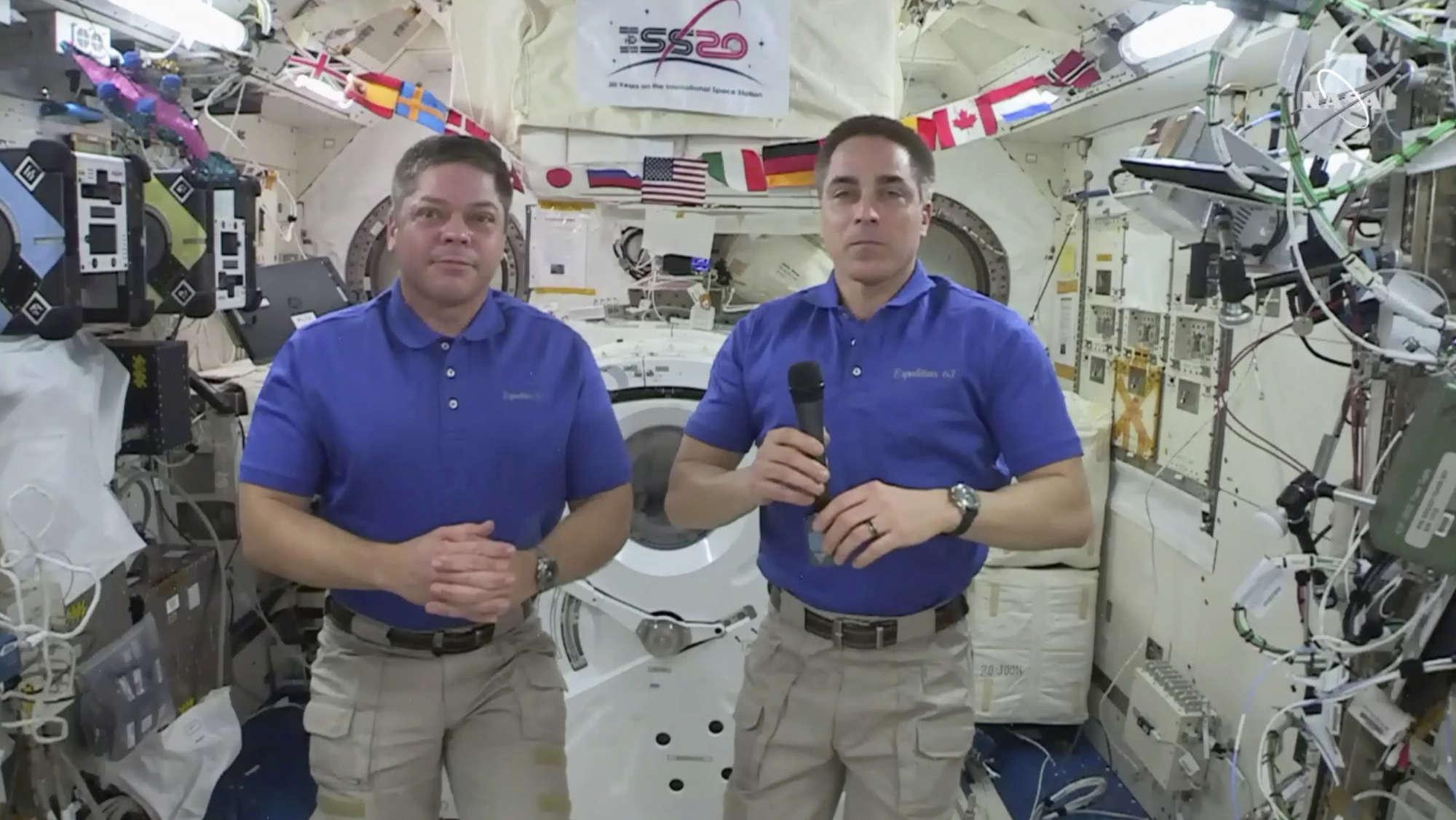 NASA astronaut Chris Cassidy, right answers a question as fellow astronaut Robert L. Behnken listens during an interview aboard the International Space Station