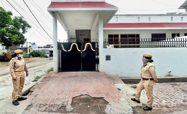 Police personnel stand guard outside the residence of Dubey at Krishna Nagar in Lucknow on July 9