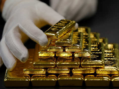 Gold inches lower as firm dollar offsets falling equities