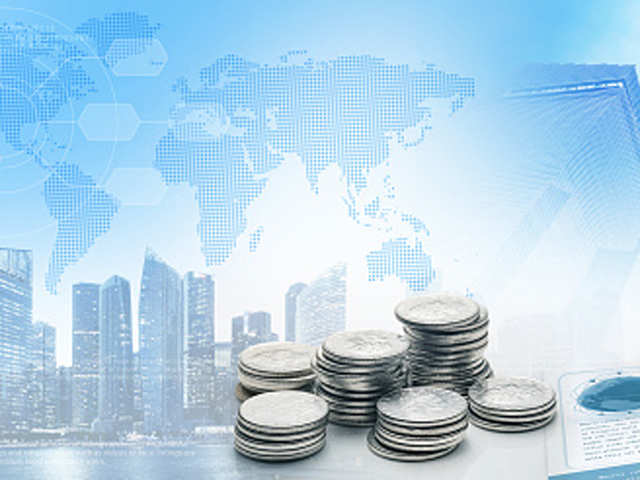 Picture of coins on table with background of a city and the world map representing finance all over the globe.