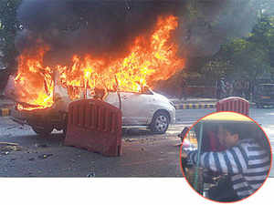 THE FIRST PICTURES: The Toyota Innova carrying the Israeli diplomat that burst into flames after the explosion in New Delhi on Monday. INSET: The injured woman being taken to the embassy after the incident