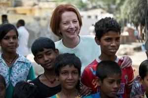 Prime Minister of Australia Julia Gillard (C) poses with children during her visit to Asha Education project site to meet slum students in New Delhi on October 16, 2012. Australian Prime Minister is on a three day state visit to India till October 17.