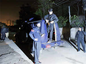 Police officers gather beside an armored vehicle near the site of rocket attack by militants in Peshawar, Pakistan on December 15, 2012. (AP)