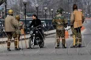Paramilitary jawans inquires a motorcyclist on the fourth consecutive day of curfew imposed in the Kashmir valley, following the hanging of Parliament attack convict Afzal Guru, in Srinagar. Curfew has been lifted from Nigeen, Lal Bazaar and Zakura police station areas in the city.