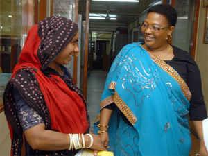 Zimbabwean Deputy Prime Minister Thokozani Khupe is watched by Managing Director of India's Shri Mahila SEWA Sahkari Bank Jayshree Vyas as she interacts with a bank customer in Ahmedabad. (*Pic: BCCL)