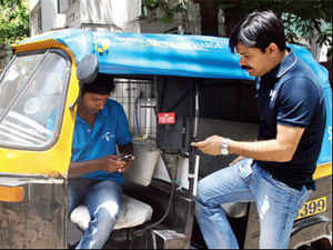 Uninor Maharashtra circle head Ritesh Singh gets his mobile recharged by an actual rickshaw driver in Mumbai