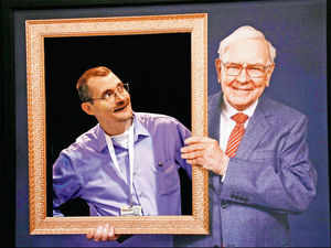 A Berkshire Hathaway shareholder poses behind an empty picture frame, next to a photograph of Berkshire chairman Buffett, at the company's annual meeting in Omaha.