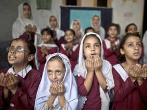 Security was tightened around a government girls' school in Rawalpindi after a letter allegedly sent by the Pakistani Taliban warned that it would be blown up. In Pic: Students praying in a Rawalpindi government girls school.