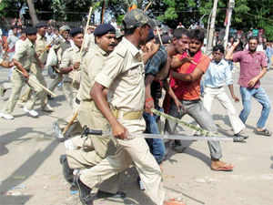 People thrash a man whom the police detain and take away for questioning after a bomb blast outside the venue of BJP's Hunkar rally in Patna on Sunday.