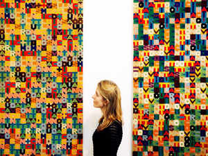 A Christie's employee poses with Alighiero Boetti's artworks 'Addizione' and 'Sottrazione' at Christie's Mayfair gallery in London. All proceeds from the auction will benefit the CalArts School of Art, supporting student artists by providing enhanced creative space.