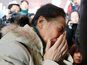 A relative of a passenger onboard Malaysia Airlines flight MH370 crying at the Beijing Capital International Airport.