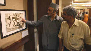 ICCR President Karan Singh with curator Aditya Arya admiring a rare photograph, shot by lensman the Late Kulwant Roy, on display at the exhibition, 'History in the Making', in New Delhi on Friday.(PTI)