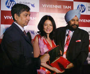Designer Vivienne Tam, Ravi Swaminathan (L) and Senior Vice President, Satjiv S Chahil, displays a laptop during its launch in New Delhi on Wednesday. (PTI)