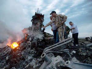 People inspect the crash site of a passenger plane near the village of Hrabove, Ukraine. (AP)
