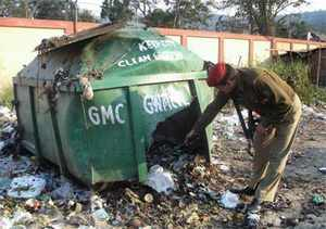 A security man inspects the garbage bin where an IED blast took place, in Guwahati on January 1, 2009.