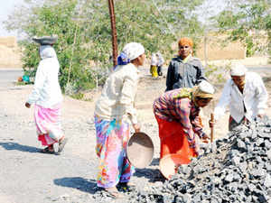 Workers covered under the MGNREGS programme work on a road construction project.