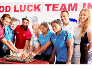 Indian men's and women's hockey team members with staff cutting a cake during an event to wish good luck to them in New Delhi for upcoming FINTRO FIH World League Semi-Finals.