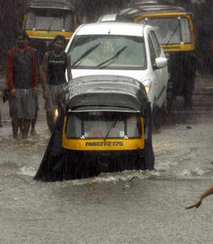 Vehicles move through a flooded road after heavy rains in Mumbai on Tuesday. Reuters Photo Click on picture for more