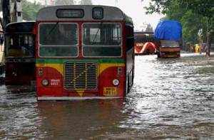 Vehicles move through a water-logged street after rains in Mumbai on Tuesday. Click on picture for more images...