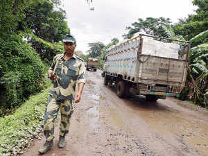 In pic: A Border Security Force soldier patrols as trucks carrying goods cross the India-Bangladesh check-post in West Bengal, India, June 20, 2015.