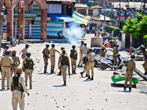 File photo: A protester throws bricks and stones at policemen amid tear gas smoke during a protest in Kashmir in Srinagar, Friday, June 26, 2015.