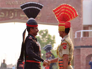In Pic: Pakistani Rangers (L) and Indian Border Security Force (BSF) personnel shake hands during the daily beating of the retreat ceremony at the India-Pakistan Wagah Border.