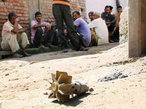 In pic: Villagers looking a mortar shell allegedly fired from the Pakistan side at Abdullian village in R S Pura Sector, about 35 kms from Jammu on August 28, 2015.