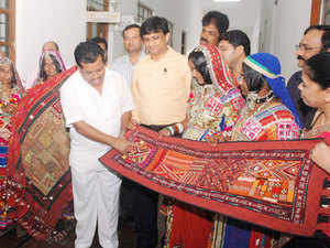 Labour Minister Parameshwar Naik seen admiring the traditional Embroidery work by National Award Winning artist Ambu Gowri Bai and Banjara community sister colleagues during the MOU signing ceremony to develop the traditional art skill between Department of Employment and Training, KVTSDC and Sandur Kushala Kala Kendra at Conference Hall Vikas Soudha, in Bengaluru.