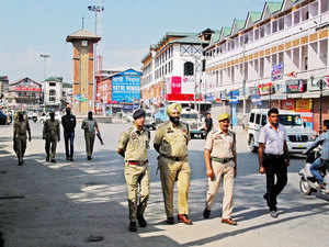 In pic: Police officials patrolling on a deserted street during a strike called by separatist groups against the killing of three youth by suspected militants in Pattan area in Srinagar.