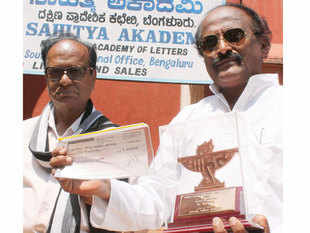 """Kannada writer Kum Veerabhadrappa arrives to return the Sahitya Academy award condemning 'silence' over the killing of rationalist M M Kalburgi and Dadri lynching. A counter protest by a set of """"nationalist minded"""" writers against fellow litterateurs returning their Sahitya Akademi awards has suddenly taken shape just ahead of the Akademi's emergency meeting."""