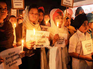 Sikhs Children taking out a candle march during their protest against the alleged desecration of religious book and Punjab firing incident in Amritsar.