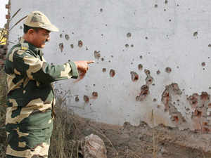 """Pakistani Rangers resorted to unprovoked firing on BSF posts along the IB in Samba and Kathua districts,"" a BSF officer said. (In pic: BSF jawan shows mortar shell marks on a wall after firing from the Pakistani side, at village Mawa in Samba district)"