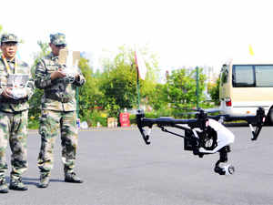 Image: A pair of militia members fly drones during a test in Shanghai, China on April 21, 2015.