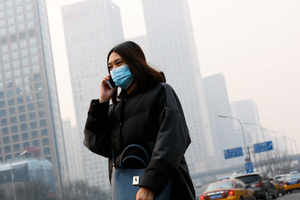 A woman wearing a mask to protect herself from pollutants walks past office buildings shrouded with pollution haze in Beijing. (AP photo)