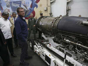 In pic: Defence Manohar Parrikar (L) and US Defense Secretary Ash Carter (C) inspect a jet engine in the hanger deck of the USS Eisenhower off the coast of Virginia, in the Atlantic Ocean, December 10, 2015.