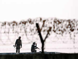 In pic: Soldiers keep guard at the perimeter fence of the Indian air force base in Pathankot.