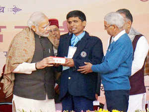 Prime Minister Narendra Modi interacting with a 'Divyang' (physically challenged) child while distributing aid & assistive devices.