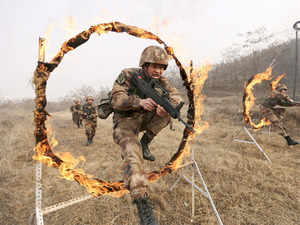 In pic: Soldiers of People's Liberation Army (PLA) Lanzhou Military Region jump through a burning obstacle during a training session at a military base in Tianshui, Gansu province, China, January 6, 2016.