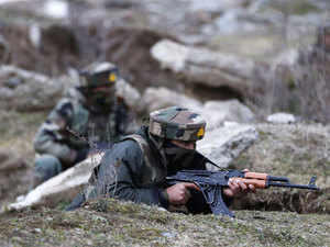 (In pic) Military personnel take up positions near a building taken over by suspected militants during clashes in the Sempora area of Pampore, some 15 kms south of Srinagar.
