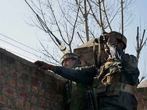 (In pic) Security personnel take position outside the JKEDI building at Sampora Pampore, near Srinagar.