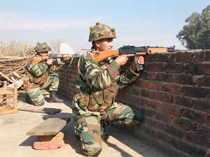 (In pic) Indian army soldiers take positions on a rooftop of a building outside the Indian airbase in Pathankot.