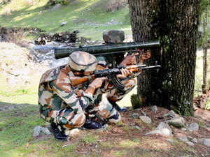 Army personnel take position at the site where militants were hiding during an encounter.