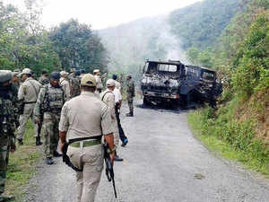 In pic: Security personnel stand alongside the smouldering vehicle wreckage at the scene of an attack on a military convoy in a remote area of Chandel district, near Imphal.