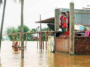 Locals watch overflowing river Tista submerged area around their houses in Basusuba in Jalpaiguri district of West Bengal.