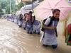 School children wade through water logged road