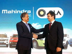 Anand Mahindra (L), chairman and managing director of Mahindra Group, and Bhavish Aggarwal, CEO and co-founder of Ola, a cab aggregator, shake hands during a news conference in Mumbai