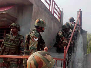 Army personnel take positions near a building where terrorists were hiding during an encounter near the under construction mini-secretariat at Allah Pir area in Poonch.