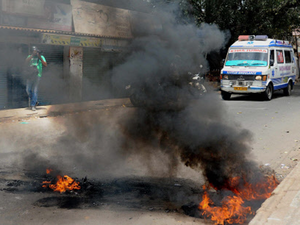 An ambulance moves at a road which was blocked by protesters by burning tyres at riot-hit Heganahalli in Bengaluru.